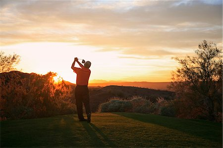 Golfer teeing off into the sunset on the golf course. Stock Photo - Premium Royalty-Free, Code: 6118-08001505