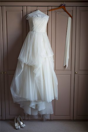 Wedding dress hanging on a wardrobe door, wedding shoes on the floor. Stock Photo - Premium Royalty-Free, Code: 6118-08140137