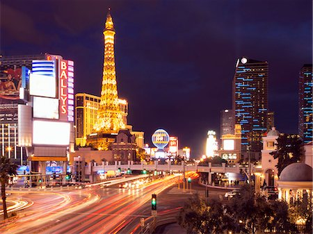 View along the Strip in Las Vegas at night, with the illuminated Paris Las Vegas Hotel and Casino in the background. Stock Photo - Premium Royalty-Free, Code: 6118-08140285