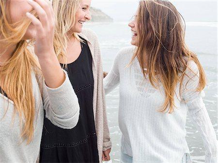 Three smiling young women walking on a beach. Stock Photo - Premium Royalty-Free, Code: 6118-08129647