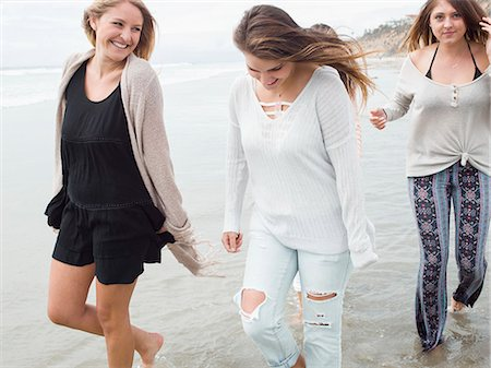 Three smiling young women walking on a beach. Stock Photo - Premium Royalty-Free, Code: 6118-08129644