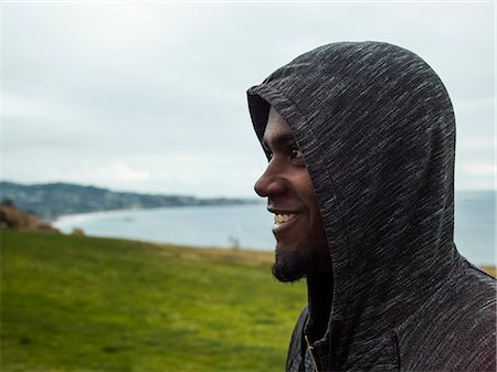 Close up of a smiling young men wearing a hoodie. Stock Photo - Premium Royalty-Free, Code: 6118-08129648
