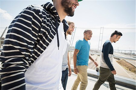 Group of young men walking along a bridge. Stock Photo - Premium Royalty-Free, Code: 6118-08129679