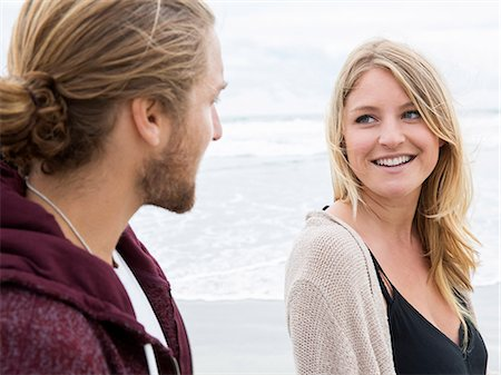 Young man and young woman on a beach, looking at each other, smiling. Stock Photo - Premium Royalty-Free, Code: 6118-08129698