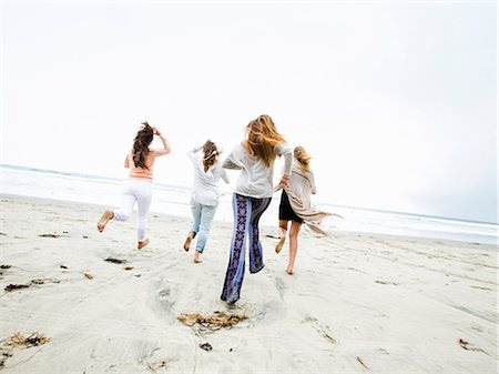 A group of young men and women running on a beach, having fun. Stock Photo - Premium Royalty-Free, Code: 6118-08129710