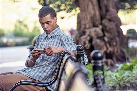 A man seated on a park bench using his smart phone Stock Photo - Premium Royalty-Free, Code: 6118-08243801
