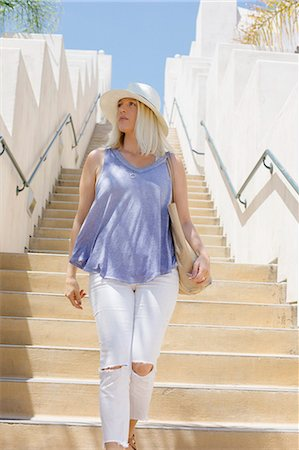Blond woman wearing a hat walking down a staircase. Foto de stock - Sin royalties Premium, Código: 6118-08282261