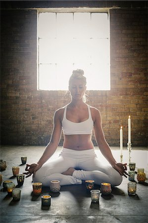 A blonde woman sitting on the floor on a yoga mat, circled by lit candles. Stock Photo - Premium Royalty-Free, Code: 6118-08202437