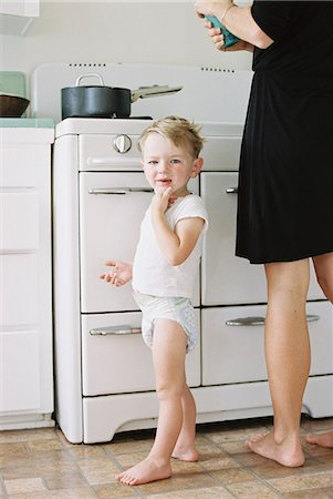 A woman and a child, a young boy standing barefoot in a kitchen. Stock Photo - Premium Royalty-Free, Code: 6118-08202510