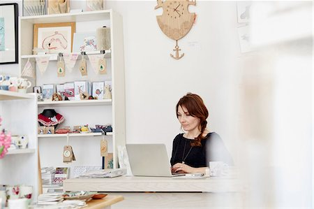 retail store - A woman sitting at a desk in a small gift shop, doing the paperwork, managing the business, using a laptop. Stock Photo - Premium Royalty-Free, Code: 6118-08202514