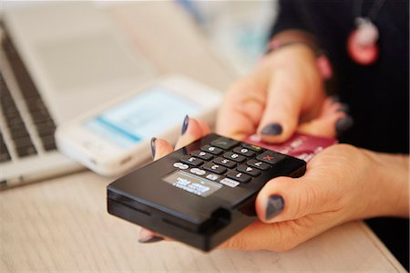 A woman's hands holding a credit card reader, processing payment or paying for goods. Stock Photo - Premium Royalty-Free, Code: 6118-08202523
