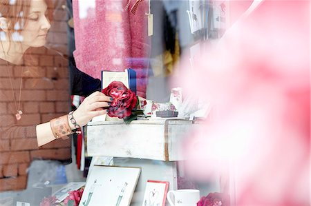 A mature woman rearranging the window display of a gift and craft store. Stock Photo - Premium Royalty-Free, Code: 6118-08202527
