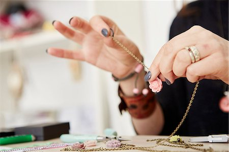A woman seated at a workbench holding a gold chain with a small floral pendant, making jewellery. Stock Photo - Premium Royalty-Free, Code: 6118-08202525