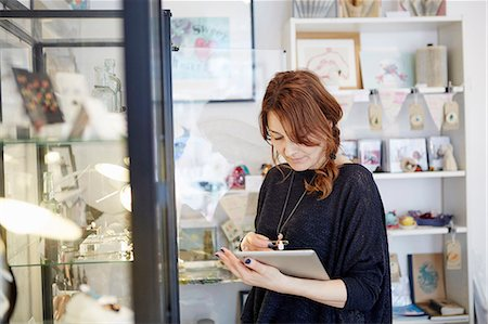 retail store - A mature woman using a digital tablet, using the touch screen, stock-taking in a small gift shop. Stock Photo - Premium Royalty-Free, Code: 6118-08202530