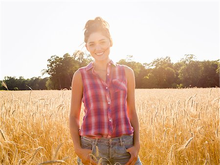A young woman standing in a field of tall ripe corn. Stock Photo - Premium Royalty-Free, Code: 6118-08220592