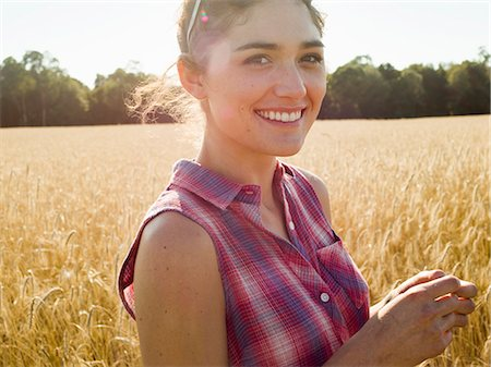 Smiling young woman wearing a checked shirt standing in a cornfield. Stock Photo - Premium Royalty-Free, Code: 6118-08220609