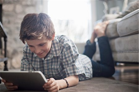 A boy lying on his front on the floor, looking at a digital tablet. Stock Photo - Premium Royalty-Free, Code: 6118-08351898