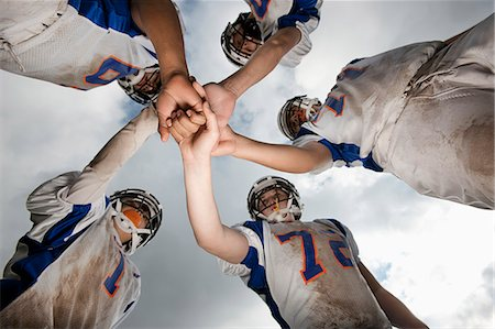 practise - A group of football players, young people in sports uniform and protective helmets, in a team huddle viewed from below. Stock Photo - Premium Royalty-Free, Code: 6118-08351830