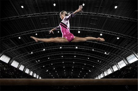 A young woman gymnast performing on the beam, balancing on a narrow piece of apparatus. Stock Photo - Premium Royalty-Free, Code: 6118-08352009