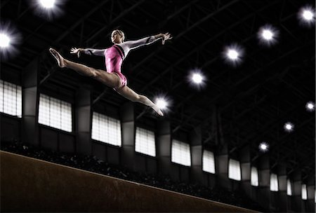 A young woman gymnast performing on the beam, balancing on a narrow piece of apparatus. Stock Photo - Premium Royalty-Free, Code: 6118-08352013