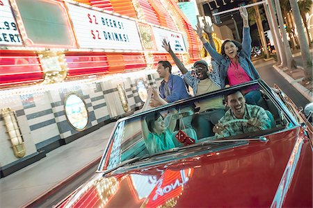 A group of friends in a red open top convertable classic car celebrating with waving arms as they drive through a city lit with neon signs. Stock Photo - Premium Royalty-Free, Code: 6118-08394244