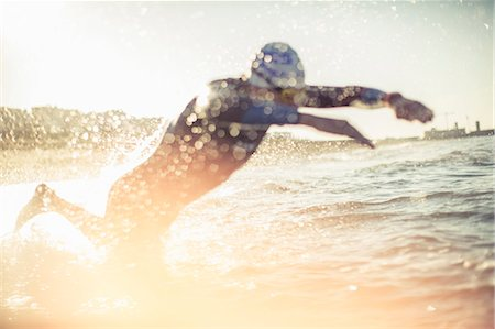 A swimmer in a wet suit running into the water, making a splash. Stock Photo - Premium Royalty-Free, Code: 6118-08399557