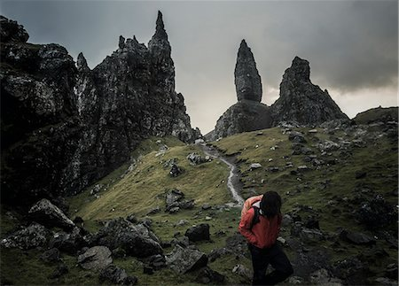 friluftsliv - Two people with rucksacks on a narrow path rising to a dramatic landscape of rock pinnacles on the skyline towering above them, under an overcast sky with low cloud. Stock Photo - Premium Royalty-Free, Code: 6118-08399659
