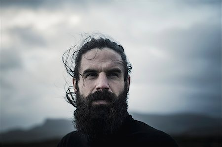 rugged landscape - A man with black hair, a full beard and moustache. Stock Photo - Premium Royalty-Free, Code: 6118-08399695