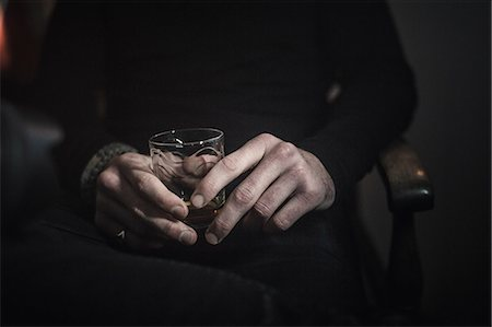 A man's hands holding a glass of whisky. Stock Photo - Premium Royalty-Free, Code: 6118-08399704