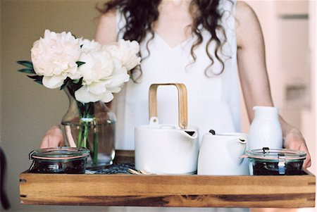 Woman carrying a tray with a teapot and a vase of white roses. Stock Photo - Premium Royalty-Free, Code: 6118-08313745
