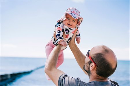 A father lifting his baby daughter in a sun bonnet up in the air, Stock Photo - Premium Royalty-Free, Code: 6118-08313795