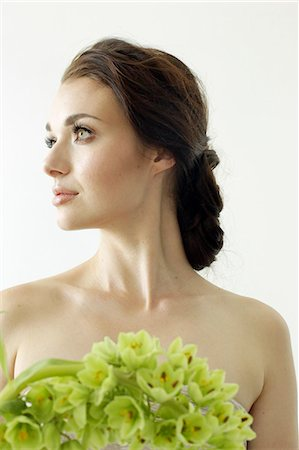 Portrait of a woman with brown hair tied in an elegant bun, wearing a dress with a green flower wreath. Stock Photo - Premium Royalty-Free, Code: 6118-08313735