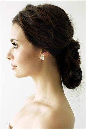Portrait of a woman with brown hair tied in an elegant bun. Stock Photo - Premium Royalty-Free, Code: 6118-08313738