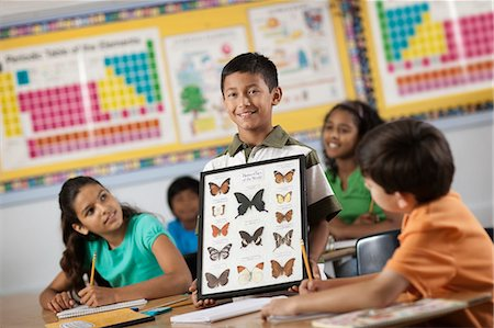 A boy standing in front of classmates, holding up a frame with butterfly specimens. Stock Photo - Premium Royalty-Free, Code: 6118-08488290