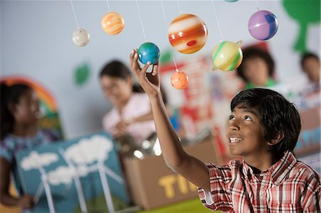 preteen models asian - A boy looking up at a display of the planets, a presentation of the planetary system. Stock Photo - Premium Royalty-Free, Code: 6118-08488227