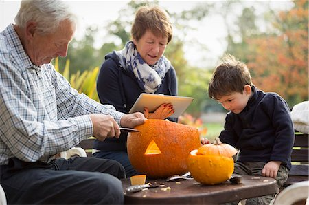 Two adults and a small child with large pumpkins, creating pumpkin lanterns for Halloween. Stock Photo - Premium Royalty-Free, Code: 6118-08488472