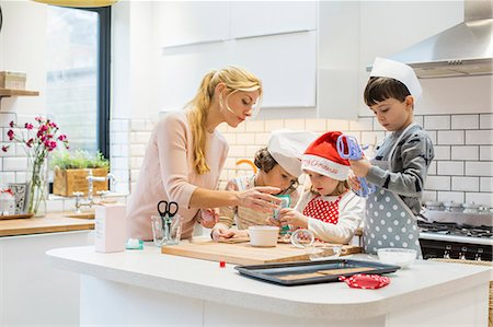 A woman and three children working together, making a gingerbread house, and icing the gingerbread. Stock Photo - Premium Royalty-Free, Code: 6118-08521749