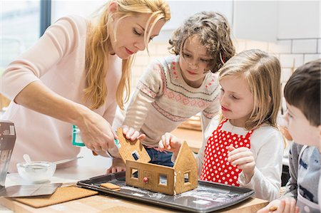 A woman and three children creating a baked gingerbread house. Stock Photo - Premium Royalty-Free, Code: 6118-08521750