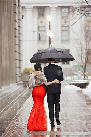 A woman in a long red evening dress with fishtail skirt and a fur stole, and a man in a suit, walking through a city. Stock Photo - Premium Royalty-Free, Code: 6118-08521880