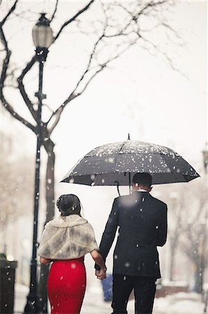 A woman in a long red evening dress and a man in a suit, walking through snow in the city. Stock Photo - Premium Royalty-Free, Code: 6118-08521890