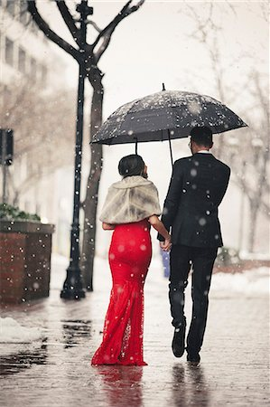 A woman in a long red evening dress with fishtail skirt and a fur stole, and a man in a suit, walking through snow in the city. Stock Photo - Premium Royalty-Free, Code: 6118-08521891