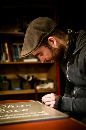 A sign writer working with a loaded brush painting a line freehand on the edge of a sign. Stock Photo - Premium Royalty-Free, Code: 6118-08659687