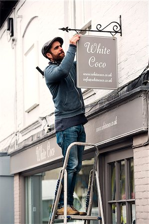 A man on a ladder fixing a painted name sign onto a bracket on a shopfront. Stock Photo - Premium Royalty-Free, Code: 6118-08659694