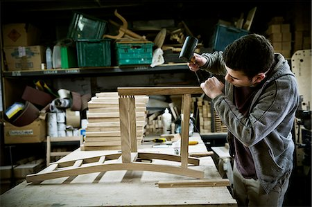 A man working in a furniture maker's workshop assembling a chair. Stock Photo - Premium Royalty-Free, Code: 6118-08659744