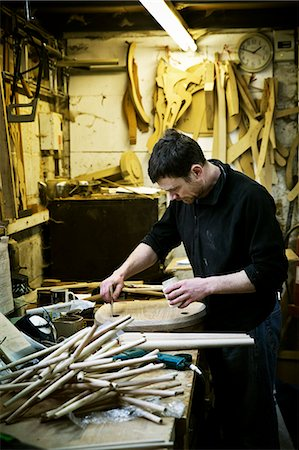 A man working in a furniture maker's workshop. Chair legs on the bench. Stock Photo - Premium Royalty-Free, Code: 6118-08659752