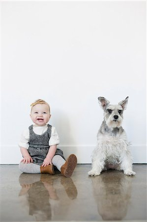 A small girl and a dog sitting side by side. Stock Photo - Premium Royalty-Free, Code: 6118-08659707
