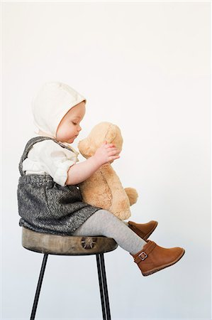 A young child, a girl sitting on a tall stool holding a teddy bear. Stock Photo - Premium Royalty-Free, Code: 6118-08659709