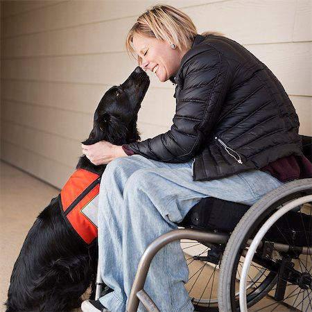 A mature woman wheelchair user with her service dog, a black Labrador, leaning in towards each other. Stock Photo - Premium Royalty-Free, Code: 6118-08659724