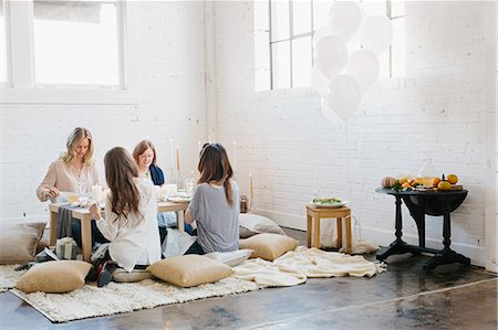 Four women seated at a low table on cushions. Stock Photo - Premium Royalty-Free, Code: 6118-08659829