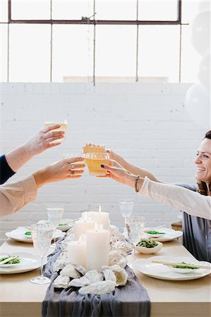 Four people raising their glasses in a toast at a meal. Stock Photo - Premium Royalty-Free, Code: 6118-08659833